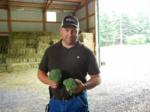 broccoli grower holding two harvested broccoli heads