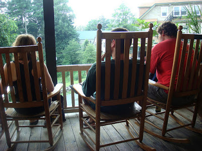 three attendees relaxing outside in rocking chairs
