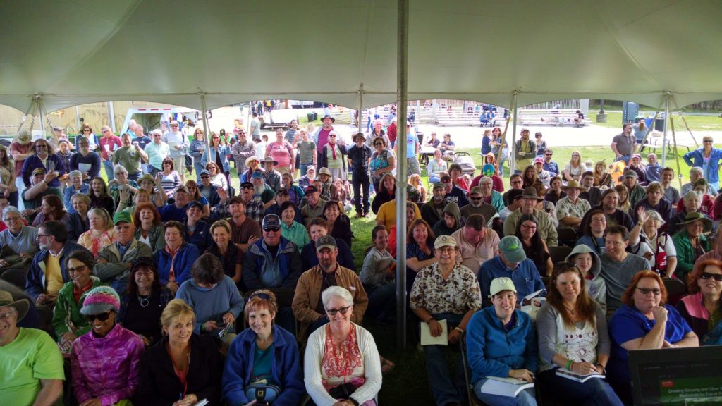 An audience of smiling people in a tent